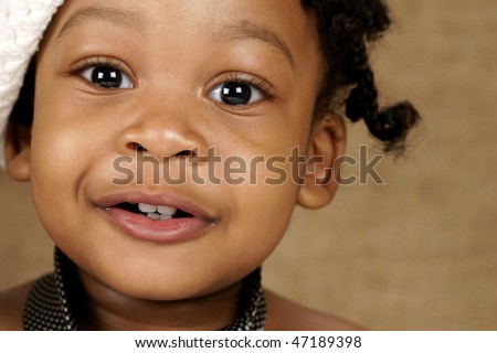 bright eyed toddler with white head wear and men's tie