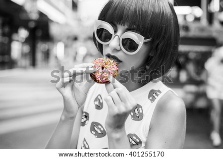 bright fashion funny girl in a blue wig biting a sweet donut on a background carousel at an amusement park. Black-and-white photography with a color separation of a donut. - stock photo