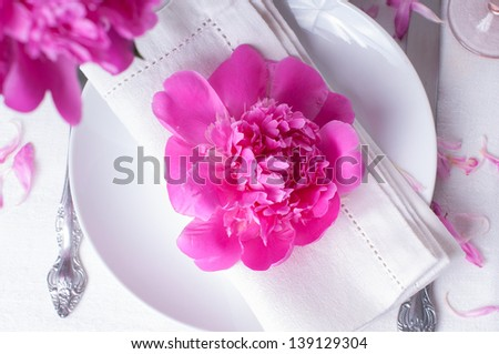 Bright festive table setting with pink peonies, candles and vintage cutlery - stock photo