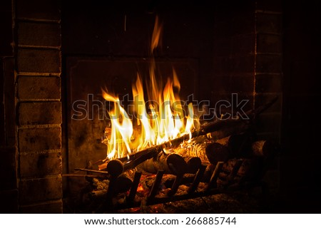 bright flame of fire burns in a fireplace in the old house in winter evening - stock photo