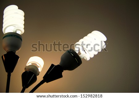 Bright, flourescent lights glowing in a dark room. - stock photo