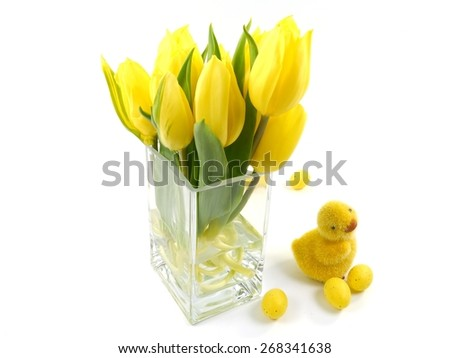 Bright flowering yellow spring tulips on a vase and an Easter decoration over white - stock photo