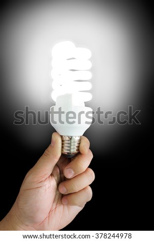 Bright fluorescent lamp on hand with black background.