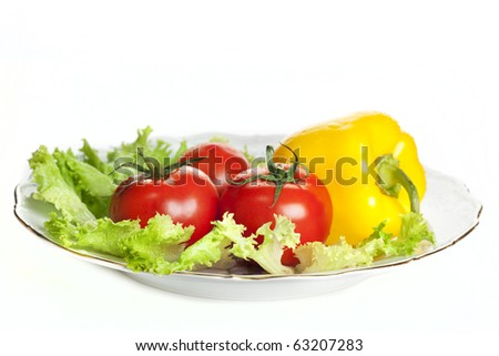 bright fresh vegetables, salad, tomato and pepper on a plate image isolated on a white background