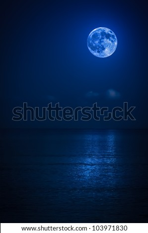 Bright full moon with reflections on a calm ocean at midnight - stock photo