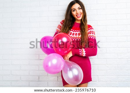 Bright funny lifestyle image to pretty young woman in casual trendy sweater having fun and holding party balloons. White urban background. - stock photo