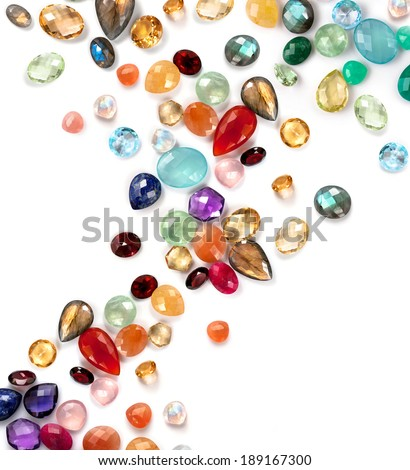 Bright gems composition on the white background. Mix of real gemstones: sapphire, ruby, garnet, lapis lazuli, rose quartz, moonstone rainbow, labradorite, amazonite, chrysoprase, citrine, amethyst ... - stock photo