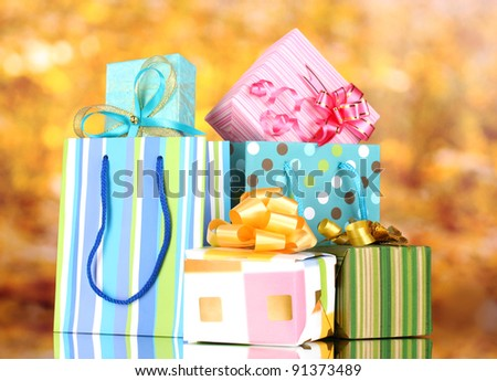 bright gift bags and gifts on yellow background - stock photo