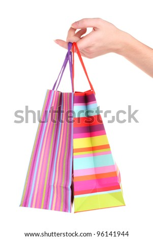 bright gift bags in hand isolated on white