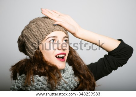 bright girl has a great idea, dressed in winter clothing, Christmas and New Year concept, studio photo isolated on a gray background