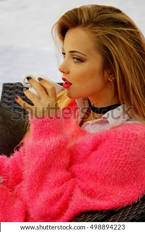 Bright girl in pink sweater and a cup of coffee in hand.