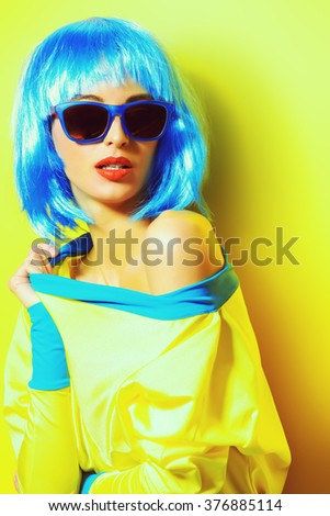 Bright glamorous girl in vivid clothes and a wig alluring over green background. Beauty, fashion. Cosmetics, hairtsyle. Optics, eyewear. - stock photo