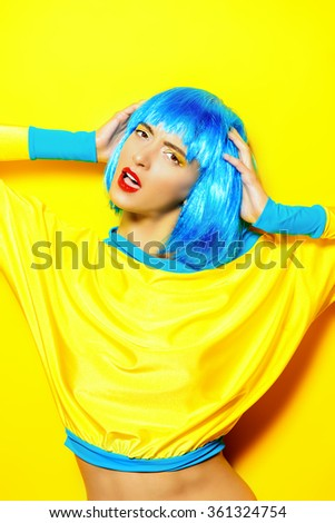 Bright glamorous girl in vivid clothes and a wig alluring over yellow background. Beauty, fashion. Cosmetics, hairtsyle. - stock photo