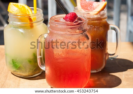 Bright glasses of lemonades with different tastes, decorated with fruits, cold, fresh, refreshing on the cafe table