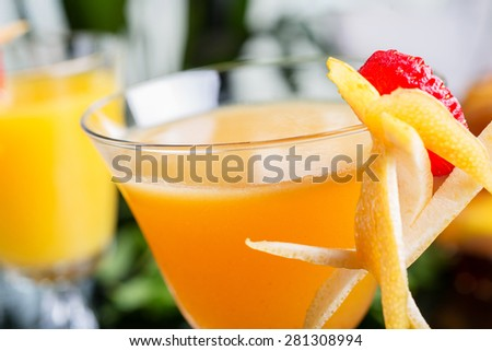 bright glasses with cold alcoholic cocktail with orange juice on a wooden table in a restaurant with creative decoration of berries, fresh mint and orange slices. soft focus - stock photo