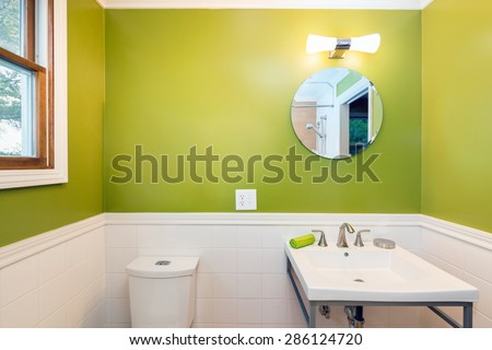 Bright Green Bathroom interior with vanity cabinet and mirror - stock photo