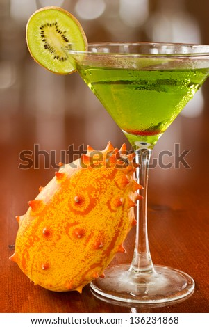 bright green cocktail served on a busy out of focus bar with horned mellon and a kiwi slice