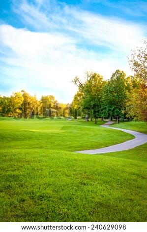 Bright green golf course surrounded by beautiful trees - stock photo