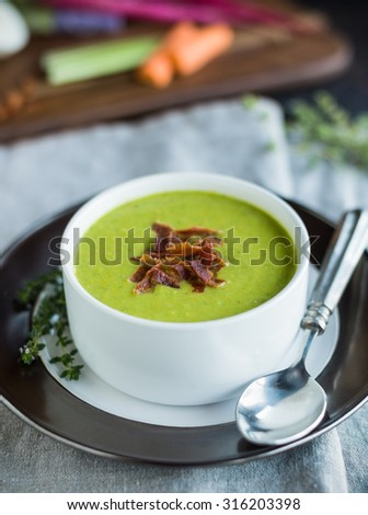 Bright green pureed pea soup with bacon garnish - stock photo
