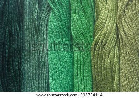 Bright green range of colors  thread floss for embroidery and needlework. Sewing threads for embroidery close-up. Multicolor sewing threads texture. Mouline.  - stock photo