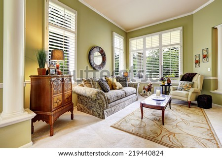 Bright green room with antique carved wood cabinet, floral sofa and coffee table - stock photo