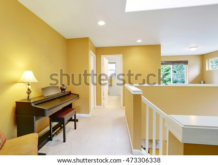 Bright hallway interior with yellow walls and piano . Northwest, USA