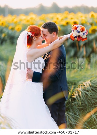 Bright happy redhair bride and groom lovingly look at each other in the sunny sunflower field