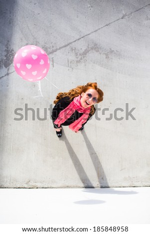 Bright happy woman holding a balloon and posing - stock photo