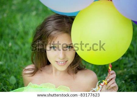 Bright happy woman holding bunch of colorful air balloons - stock photo