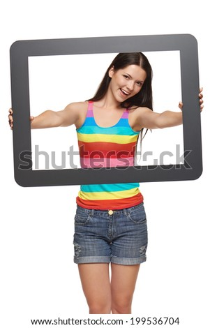 Bright happy young woman showing you tablet frame. Teen girl looking through tablet frame, over white background - stock photo