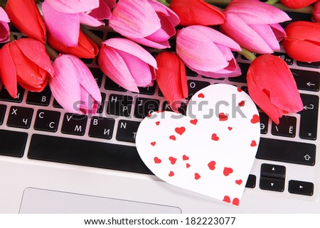 Bright heart and flowers on computer keyboard close up