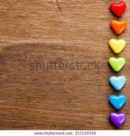 Bright hearts on wooden background - stock photo
