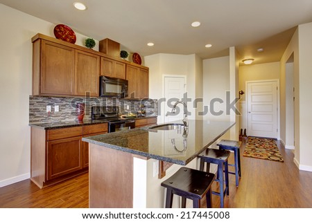 Bright house interior. Kitchen room with granite tops, island with stools