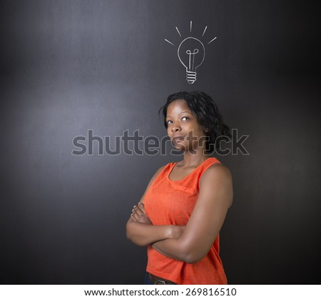 Bright idea chalk background lightbulb thinking South African or African American woman teacher or student