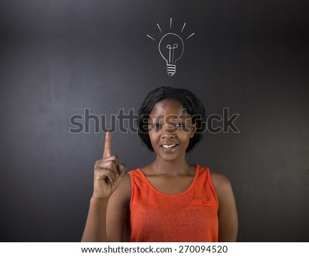Bright idea chalk background lightbulb thinking South African or African American woman teacher or student on a blackboard - stock photo