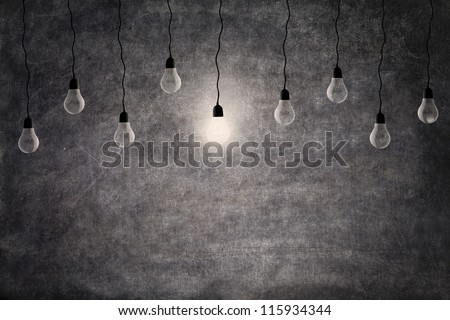 Bright idea concept: on and off light bulbs in front of empty blackboard with copy space - stock photo