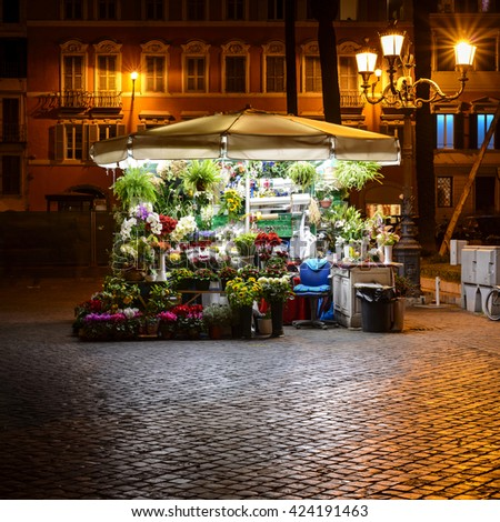 bright illuminated flower stand at night in the streets of Rome, Italy, Europe
