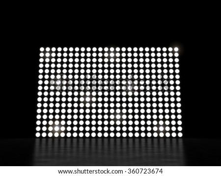 Bright illuminated wall in a dark space - stock photo