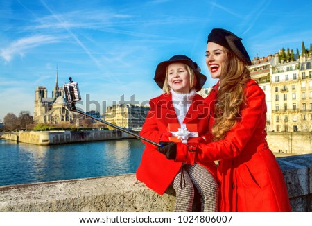 Bright in Paris. trendy mother and child travellers in red coats on embankment in Paris, France with christmas present box taking selfie using selfie stick