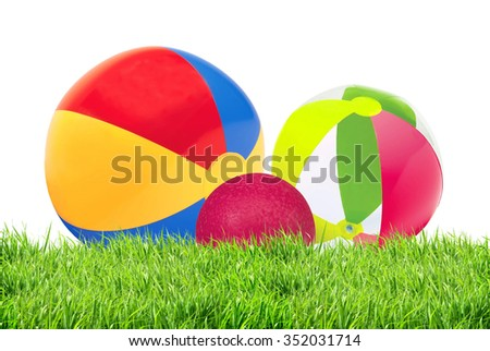 bright inflatable child balls in green grass isolated on white background - stock photo
