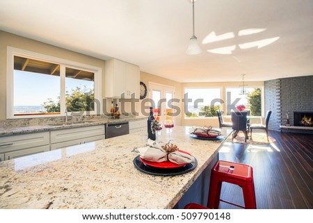 Bright interior of kitchen and large kitchen island close up with granite counter top and red stools. Also there is Elegant table setting for two. Northwest, USA