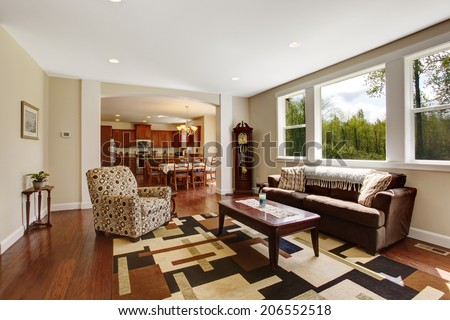 Bright ivory living room with old brown sofa, mocha armchair, wooden coffee table and antique grandfather clock