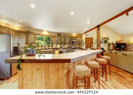 Bright kitchen room interior with large wooden bar and stainless steel fridge. View of the living room. - stock photo