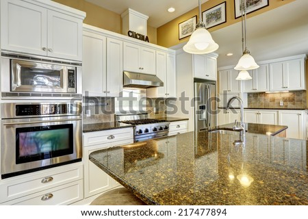 Bright kitchen room with granite tops, kitchen island and white cabinets - stock photo