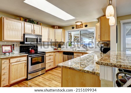 Bright kitchen room with hardwood floor, light tone wooden cabinets with granite tops and skylight - stock photo