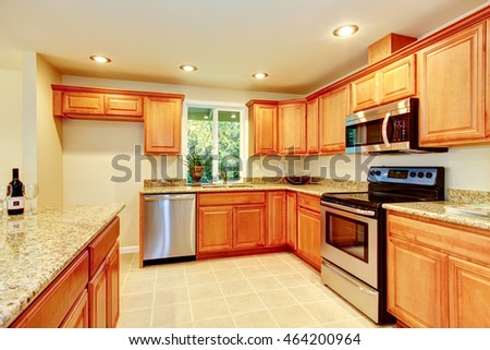 Bright kitchen room with light brown cabinets with granite counter tops and steel appliances. Northwest, USA