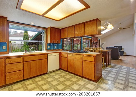 Bright kitchen room with skylight and linoleum. View of dining and living room