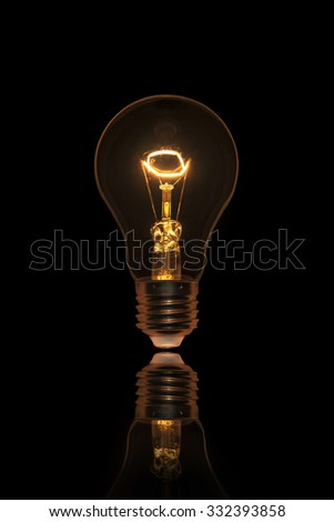 Bright Light Bulb on black background - stock photo
