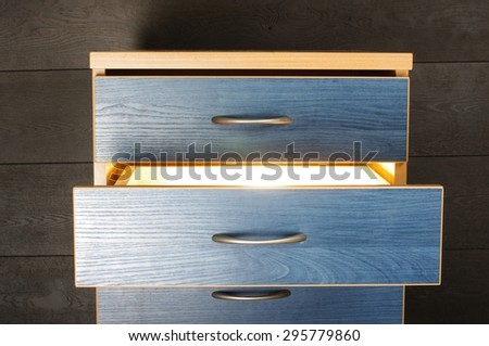 Bright light from furniture drawer - stock photo