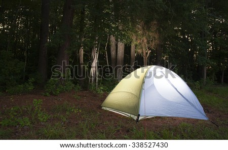 Bright light glows in a backpacking tent as darkness falls - stock photo